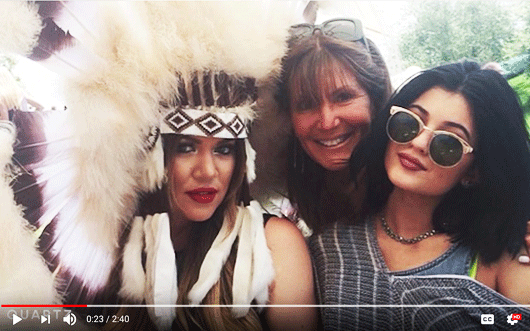 White woman, posing with friends, wearing a native american headress